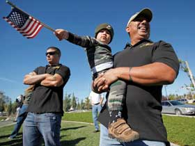 David W. Franco (left) watches a Veterans Day celebration in Moorpark, Calif., with his father, David R. Franco, who holds his godson Hunter Henry. Both Marines, the two Francos were injured during separate deployments to Iraq and have been diagnosed with traumatic brain injuries, a mental wound afflicting an estimated 10 percent of troops returning from today's wars. Both also have been diagnosed with post-traumatic stress disorder. (Chris Carlson/AP)